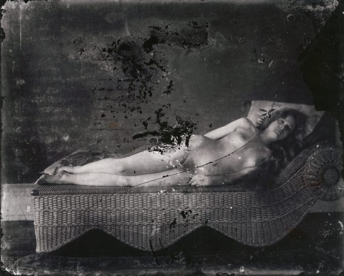Black and white photograph of a nude woman reclining on a wicker lounge chair