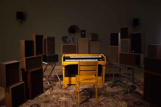 Photograph of an installation of a chair in front of a keyboard, surrounded by multiple stacked speakers