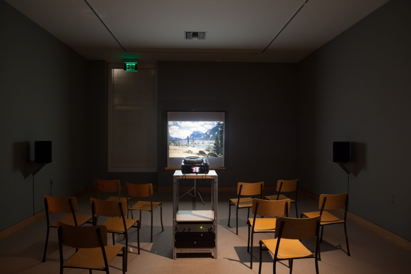 Photograph of an installation of a slide projector, flanked by chairs, projecting a color landscape onto a screen