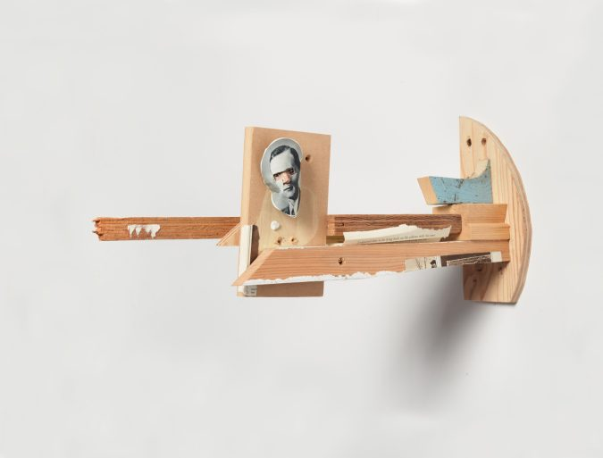 Photograph of small wooden sculpture on a grey background