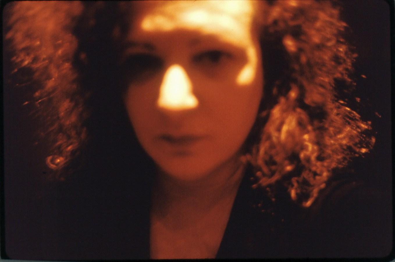 Color photograph of an out-of-focus woman's face framed by frizzy hair under orange light