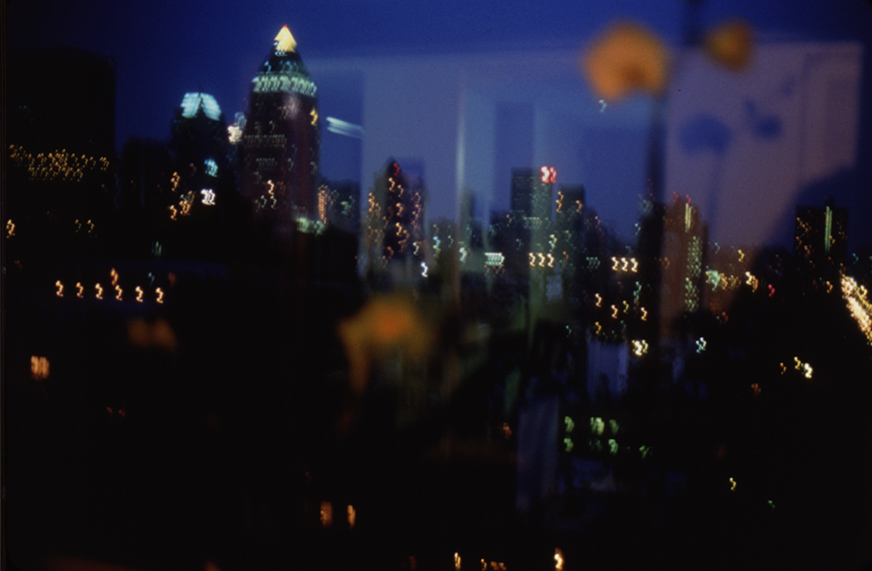 Color photograph from behind a window of an out-of-focus city skyline at night with faint reflections from the room superimposed
