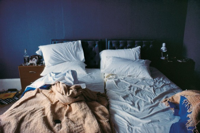 Color photograph of a bed with unmade sheets, against a blue wall