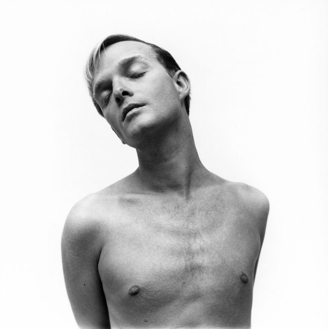 black and white photograph of a young man, shirtless, with his eyes closed, against a white background.