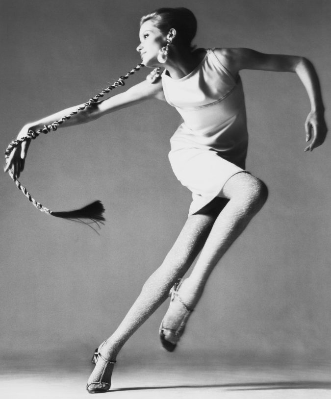 black and white photograph of a woman dancing in front of a grey background.