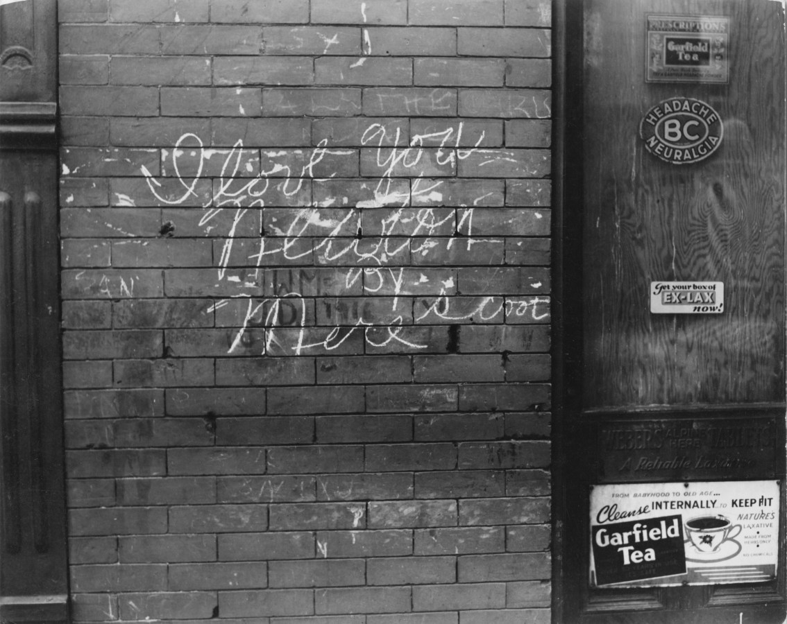 Black-and-white photograph of a brick wall with chalk grafitti that readsy, I love you Newton by Mere Scoot