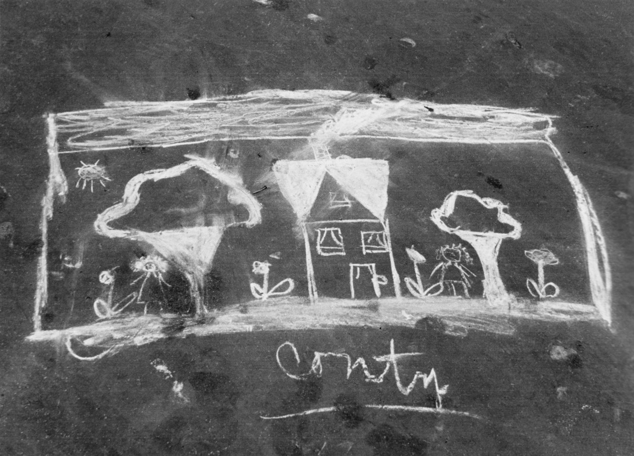 """Black-and-white photograph of a chalk drawing of a house and two trees, captioned """"Contry."""""""