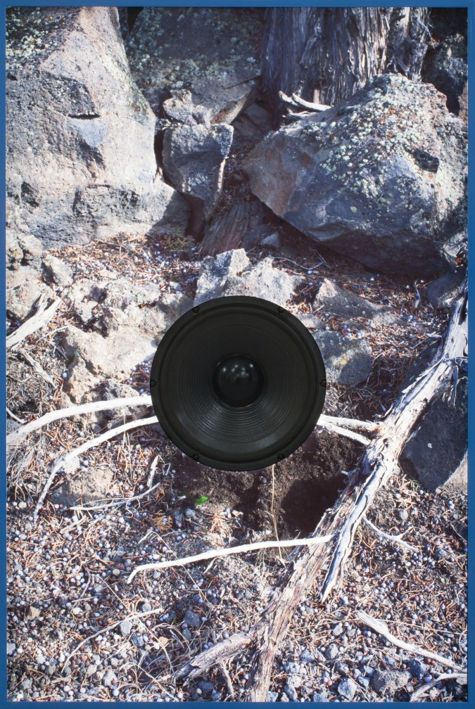 Color photograph of rocky earth cut around a black speaker