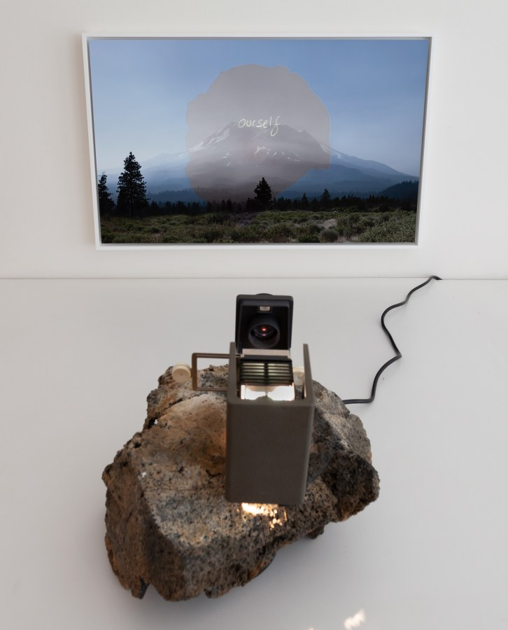 """Color photograph of a mountain with overlaid text reading """"ourself"""" being projected onto the image by a projector resting on a rock"""