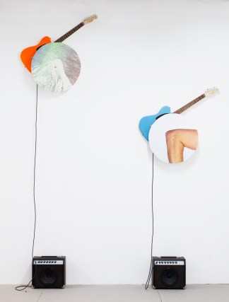 Two electric guitars mounted on a blank wall behind circular panels of a mountaintop and an elbow, connected to amplifiers on the floor below