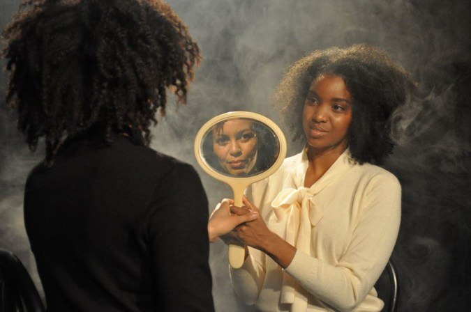 Color photograph of a young woman holding up a hand mirror to an older woman looking at her reflection