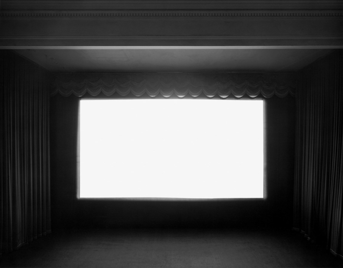 A black and white photograph of a movie theater with a bright white screen, with curtains on either side and at the top
