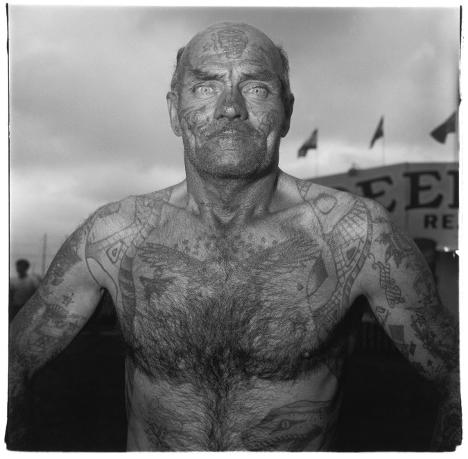 Black and white photograph of a heavily tattooed man in a carnival setting