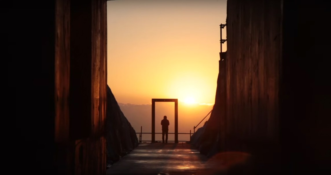 Video still of a person standing in an archway overlooking a mountain range at sunset
