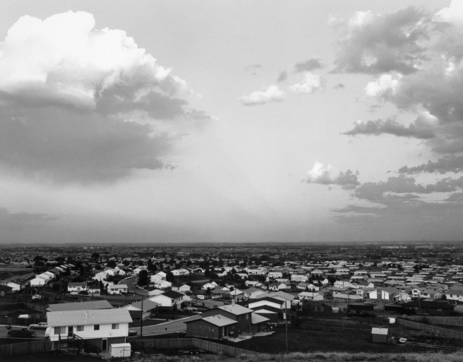 Black-and-white photograph of a suburban town and the sky above it.