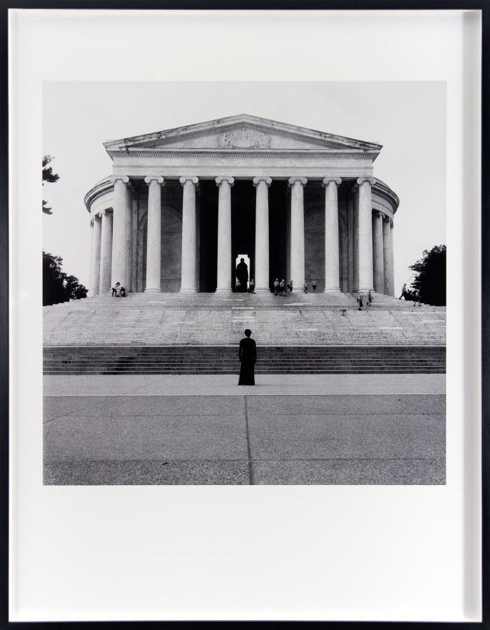 Black and white photograph of a woman standing in front of a presidential monument