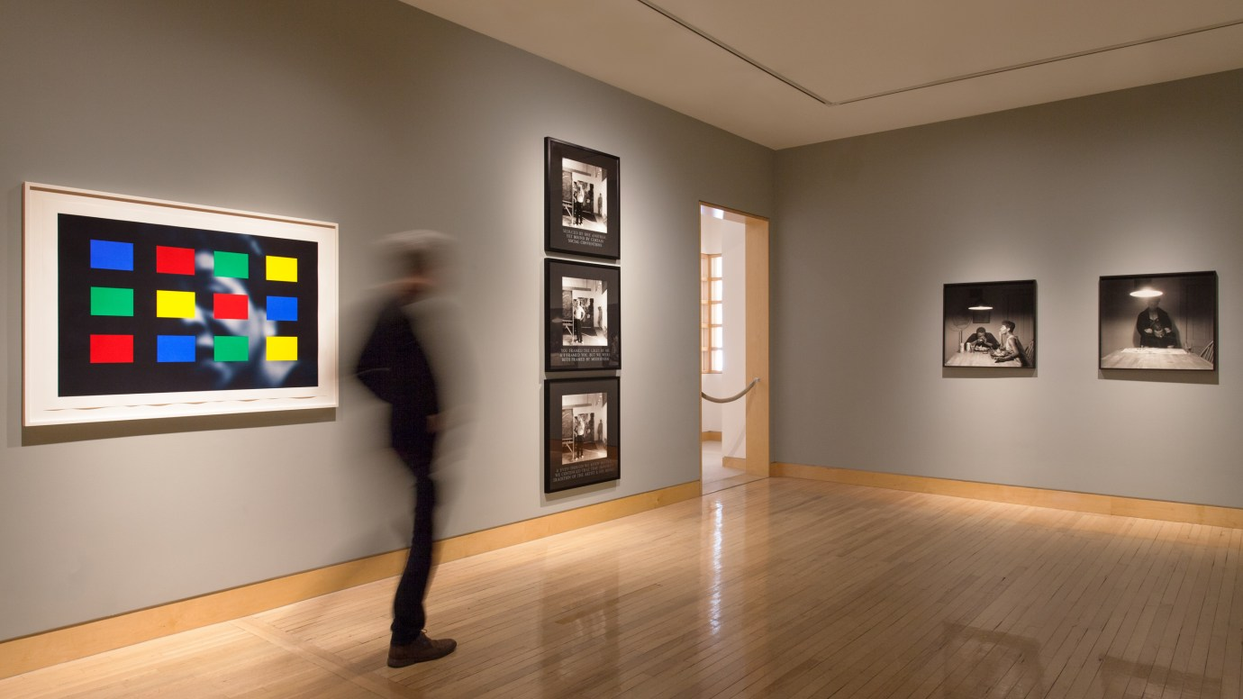 Install view of a person walking through an exhibition of photographs