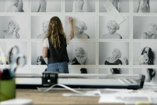Color photograph of a person making notes on prints in an art studio