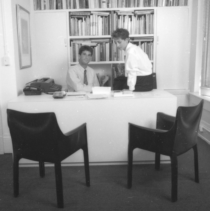 Black and white photograph of two people seated in an office
