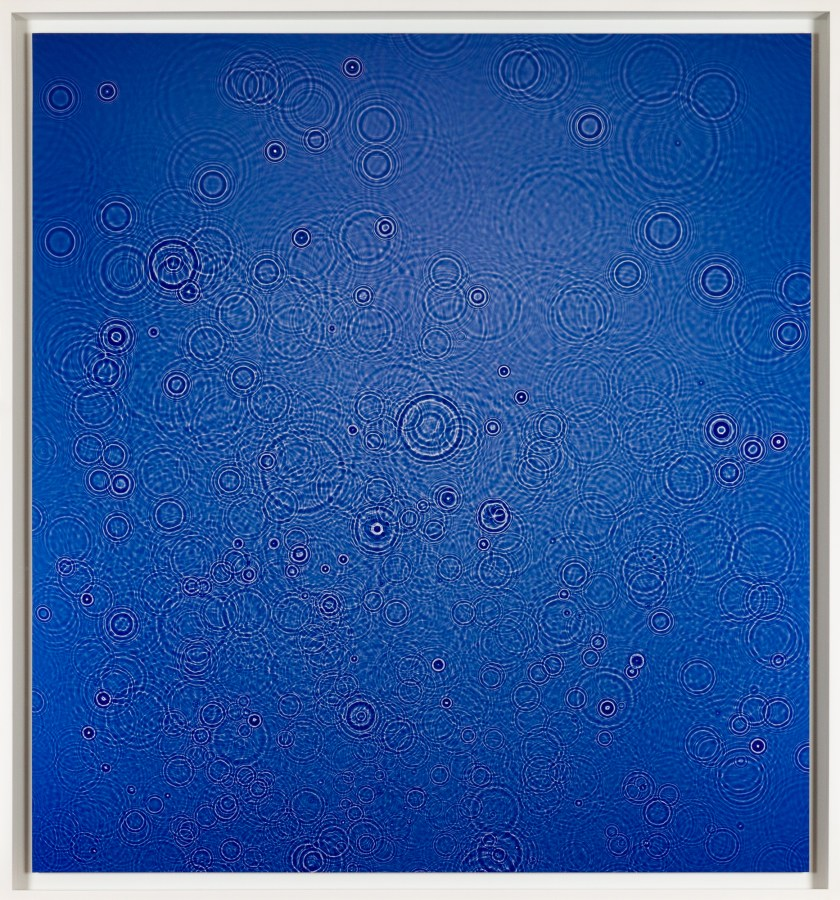 Color photogram of many concentric circular ripples in blue liquid