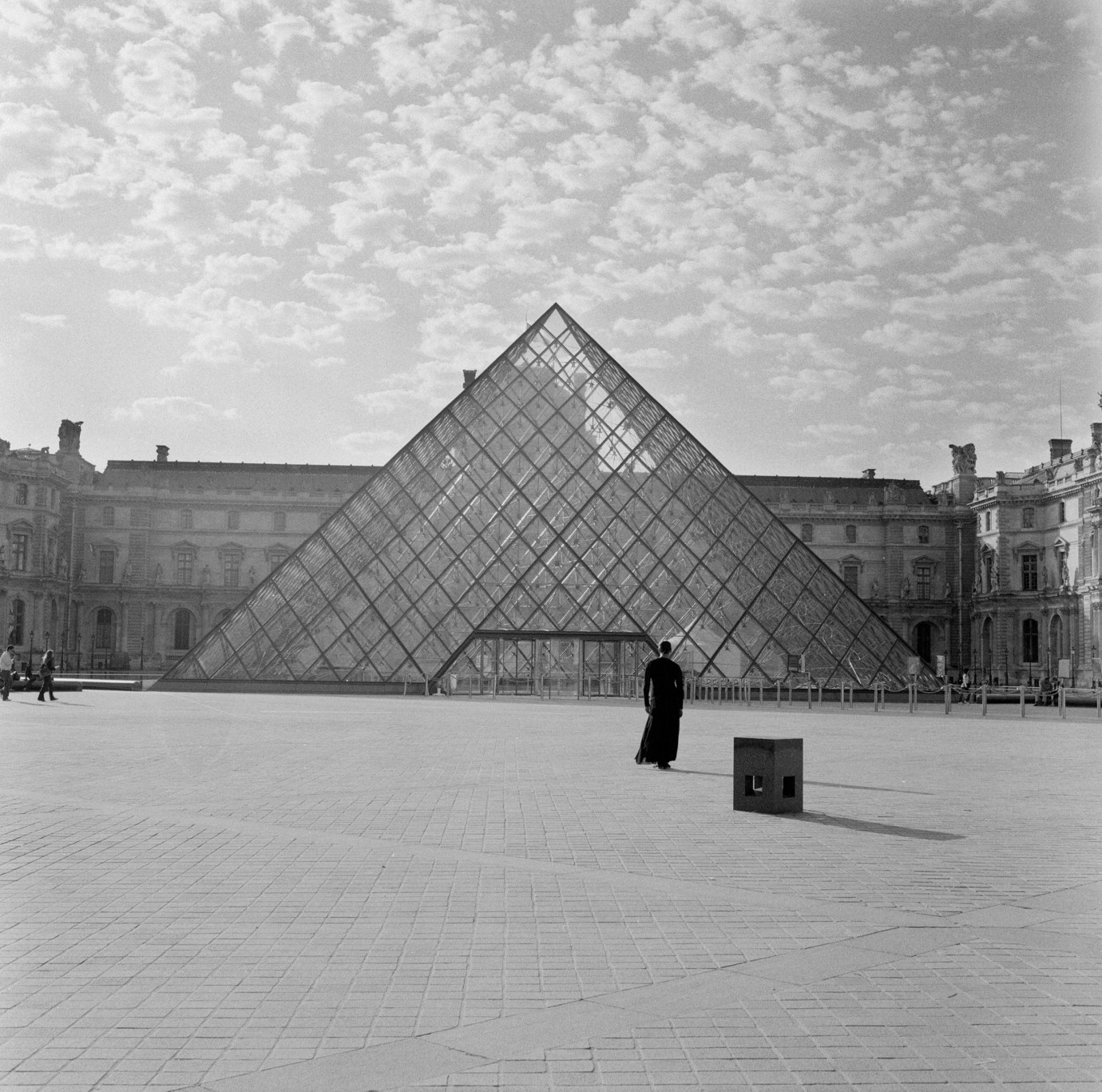 Black and white photograph of a solitary black-clad figure standing opposite of the entrance of the Louvre.