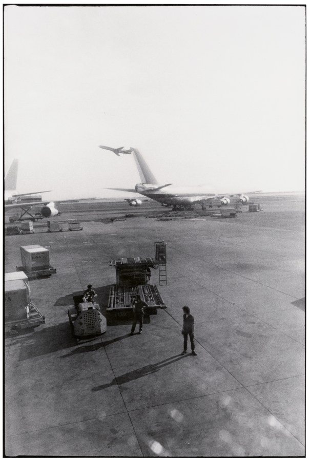 A black and white vertical photograph, taken from an airplane window while at the gate. Three men stand outside on the tarmac, with a plane in the background.