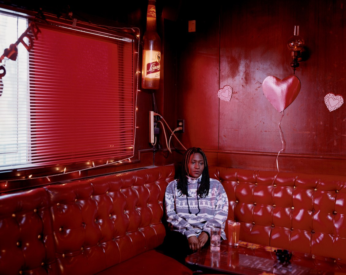 Color photograph of a young woman sitting in a red corner booth in an all-red room with paper hearts on the wall