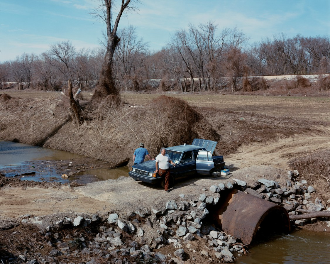 Color photograph of two men leaning on the hood of a car parked on a crossing over a wide ditch