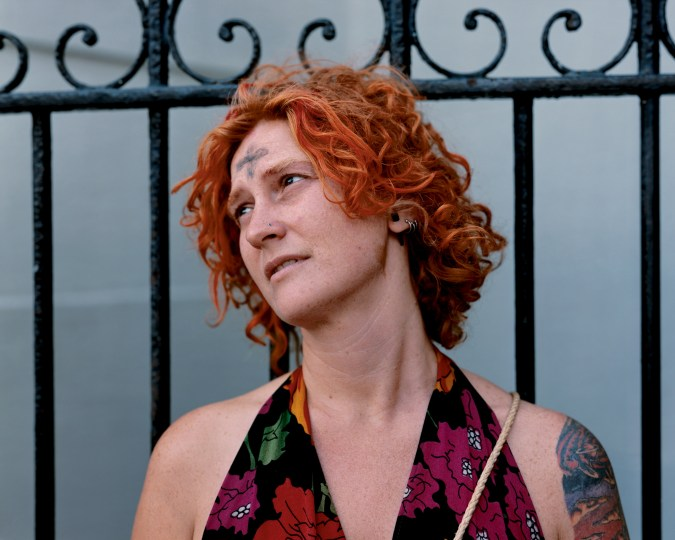 A color photograph of a white, red-haired woman in front of a fence. She has a black ash cross on her forehead.