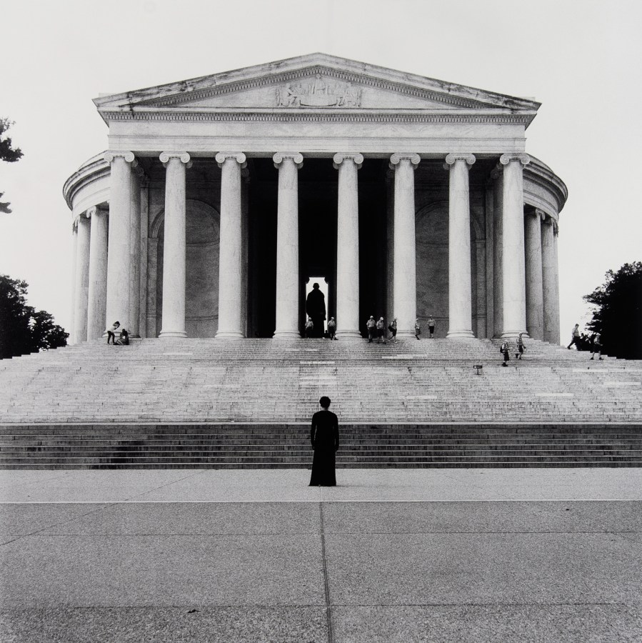 Black and white photograph showing the Jefferson Memorial in Washington DC. Jefferson's statue, silhouetted in the doorway, is mirrored by a black-clad female figure standing at the foot of the stairs, her back to the camera.