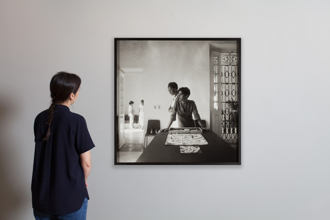 Installation view of woman looking at a framed sepia toned photograph on a grey wall depicting a woman leaning on a table in front of a boardgame and another woman staring directly into the camera behind her.