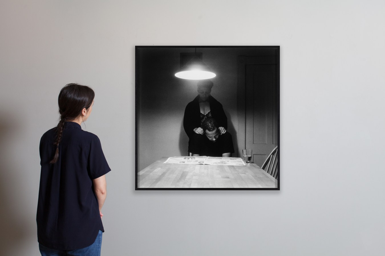 Installation view of a woman looking at a framed photograph.