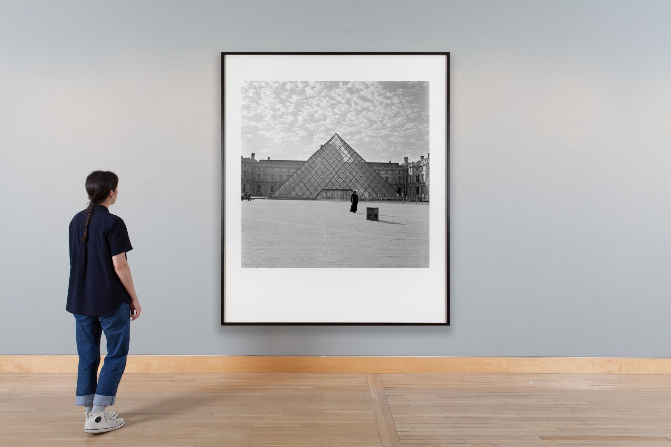 Installation photograph of a black and white image of a woman standing in front of a glass pyramid in a museum courtyard