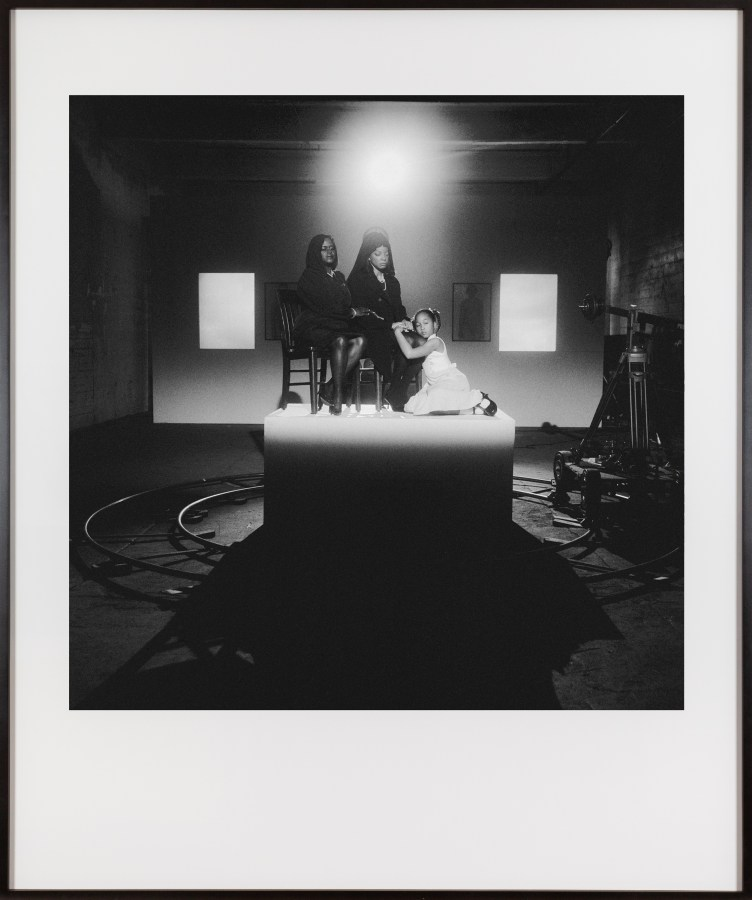 Framed black and white photograph of three people seated on a pedestal lit by a spotlight in a darkened room