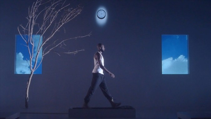 Film still from a blue-toned video depicting an African American man walking on a treadmill, flanked by a tree, two images of the sky, and a clock