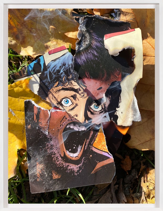 A framed color photograph of screaming faces from a comic book, torn out and lit on fire on the grass, surrounded by leaves.