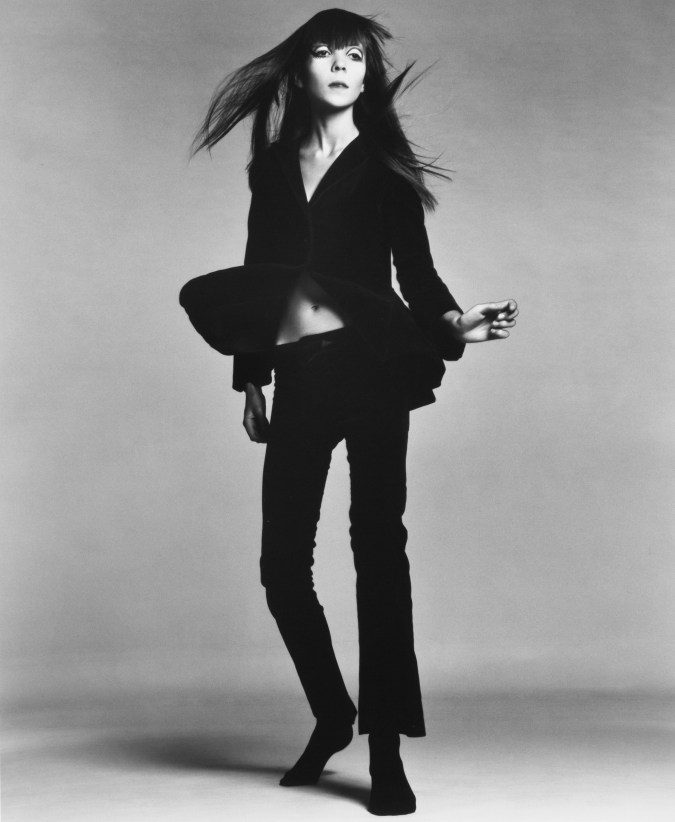 Black and white photograph of a standing in a black pantsuit