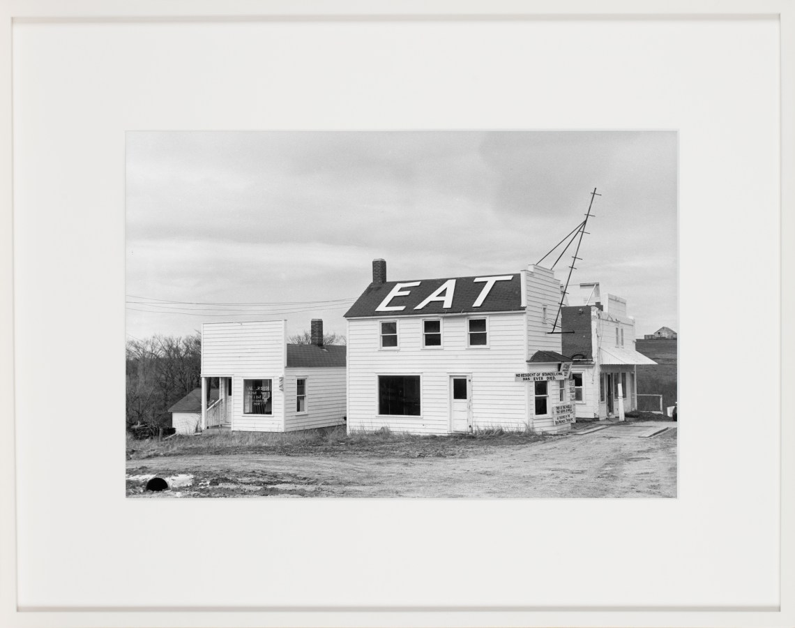 Framed black-and-white photograph of a rural two story building with the word 'eat' in large white letters on its roof.