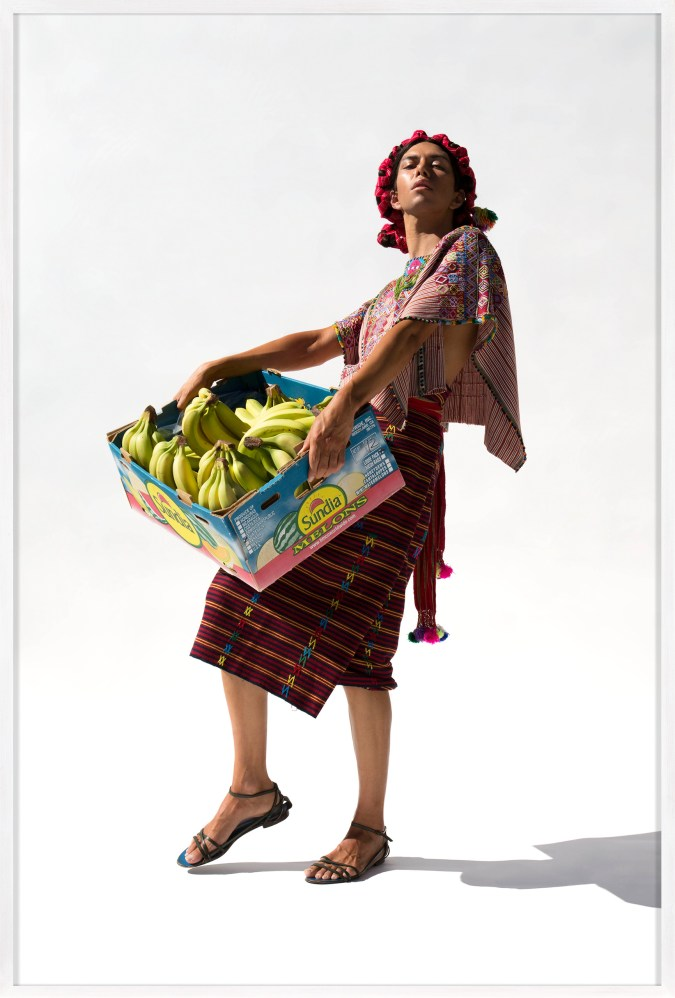 Framed color fashion photograph of a woman leaning into the sun holding a box of bananas