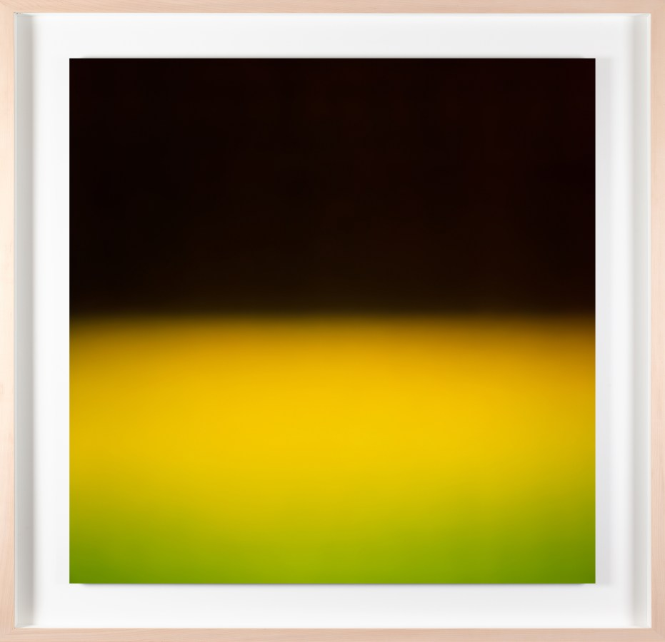A framed photograph of a bright yellow-green color field, with black in the top half.