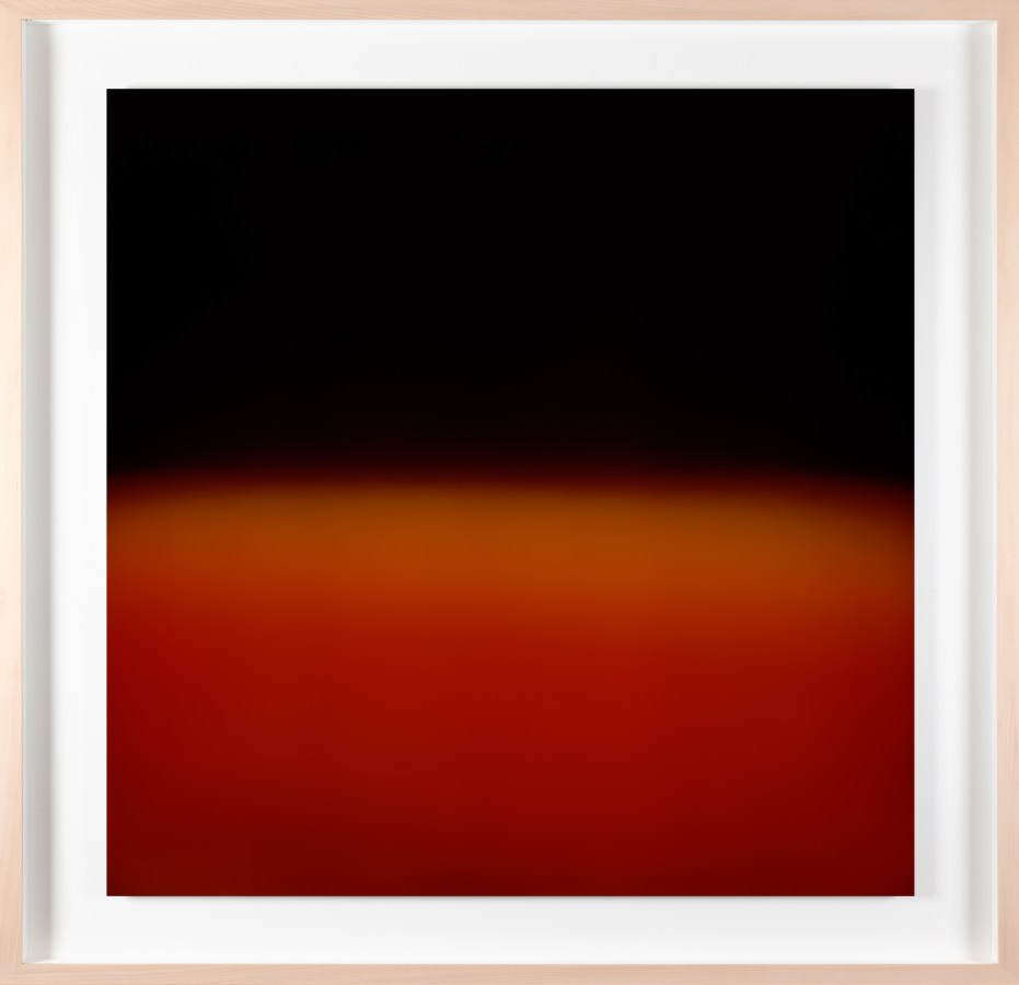 A framed photograph of a bright orange-red color field, with black in the top half.
