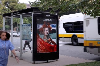 Color installation photograph of a bus shelter with an ad reading ANTI-ICON