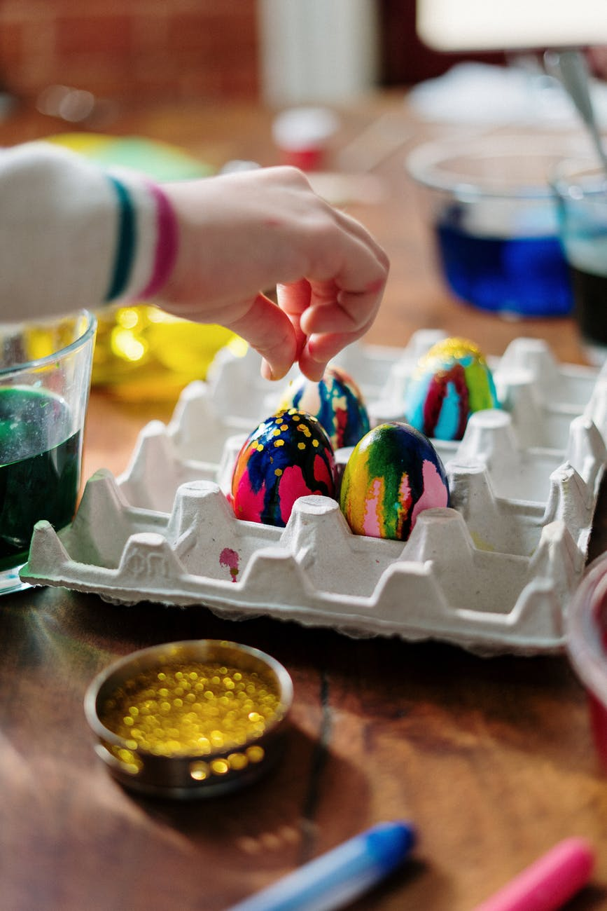 person holding easter egg on palette tray
