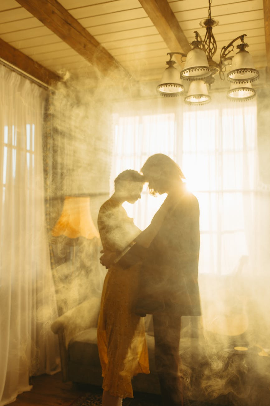 couple backlit by the sun flare through the window with curtain