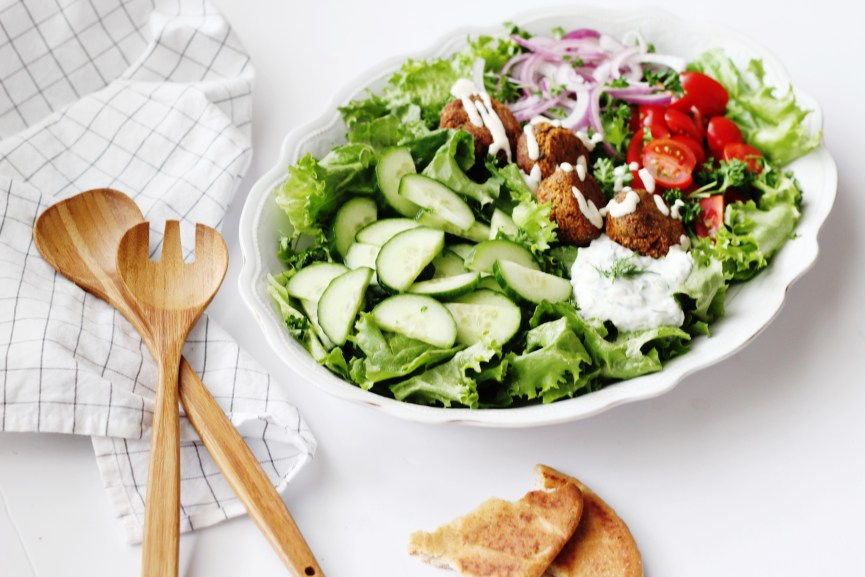 Falafel Salad in white bowl with wooden spoons