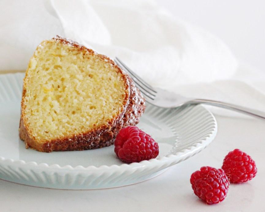 Slice of Sicilian Citrus Ricotta Bundt Cake on white plate with raspberries