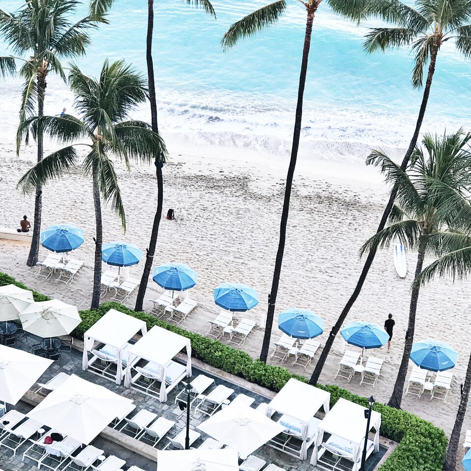 Beach view with umbrella loungers at the Moana Surfrider Hotel in O'ahu