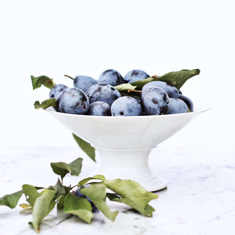Fresh plums in white bowl