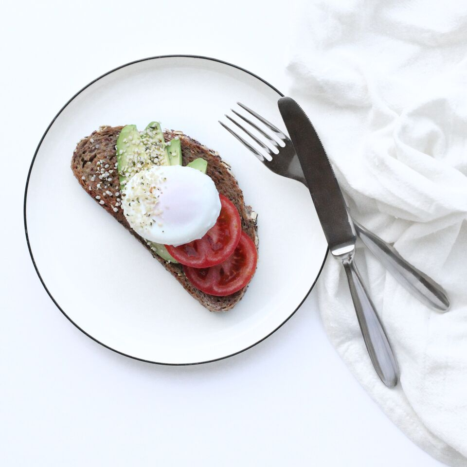 Egg and avocado toast with hemp hearts on white plate