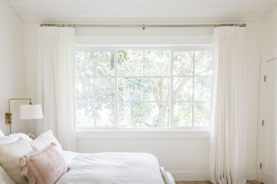 White linen drapes in a master bedroom with gold sconces